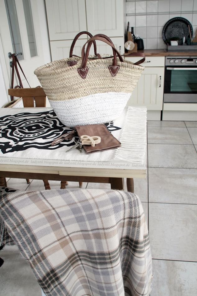 Blick in die Küche in weiß Holz, auf dem Tisch eine Korbtasche und eine Clutch mit selbstgemachtem Schlüsselanhänger