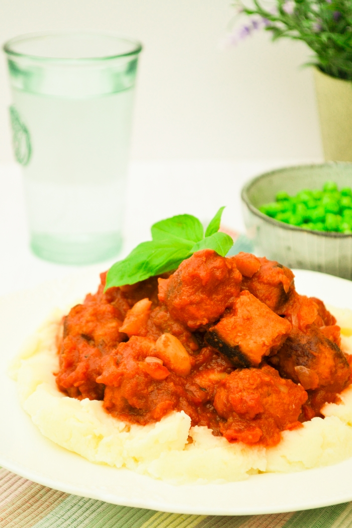 A rich tomato based stew filled with veggie sausages, mushrooms and cannellini beans. Full of the sweet flavour of tomatoes and a warmth and kick of spice from ground cumin and smoked paprika, served on a bed of creamy mashed potato with your choice of vegetables on the side. Suitable for vegetarians and vegans and loved by the whole family.