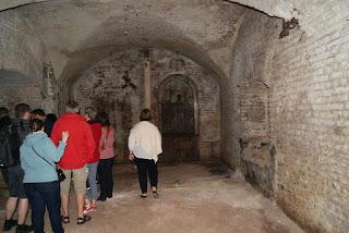 Personen stehen in einer Art Gewölbekeller