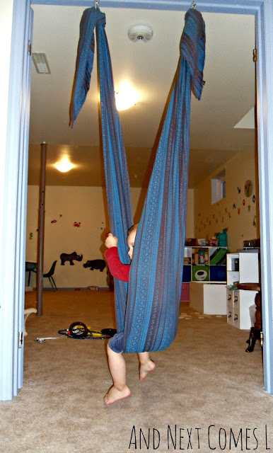 DIY sensory swing made from a woven baby wrap, hung up in a doorway