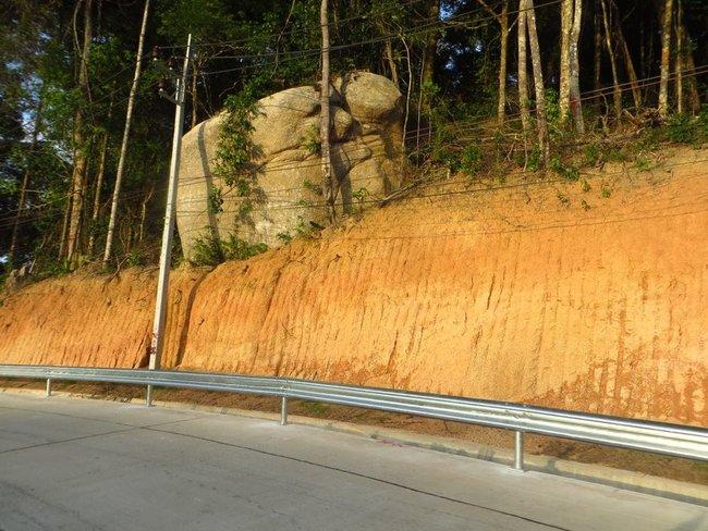 огромный камень нависает над дорогой