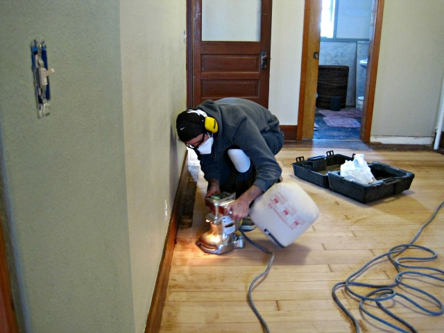 man using edging sander construction refinish floor hardwood