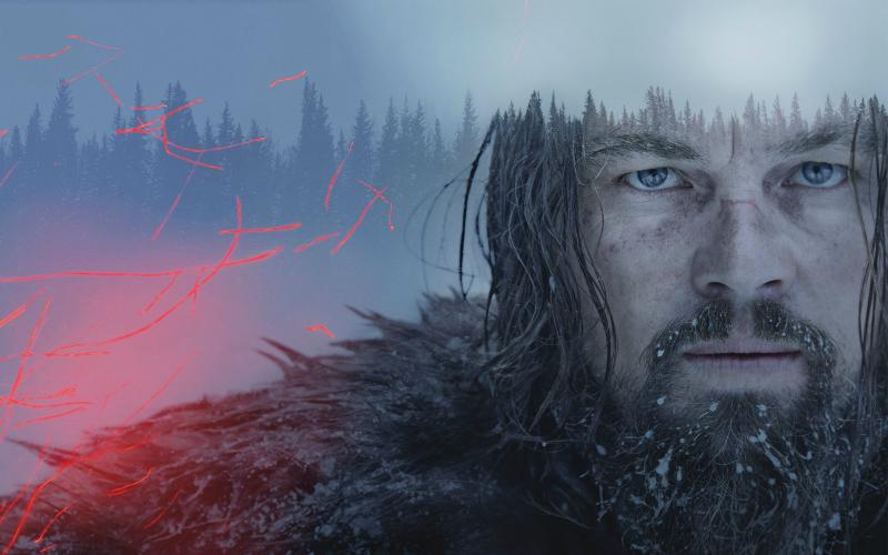 na imagem: um homem de barba e cabelo longos e sujos de neve e terra olha pra câmera fixamente, com uma expressão de dor e desamparo. Ao fundo, uma floresta enevoada de pinheiros. Ao seu lado, faíscas de um laranja fluorescente dançam no ar.