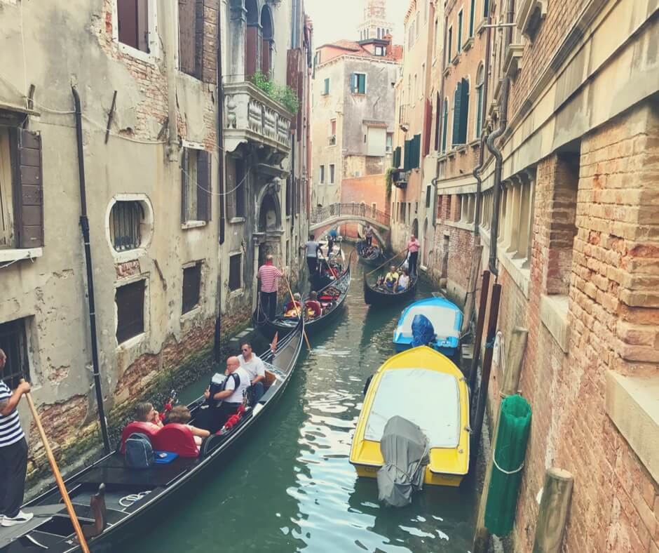 Canal in Venice, full of gondolas