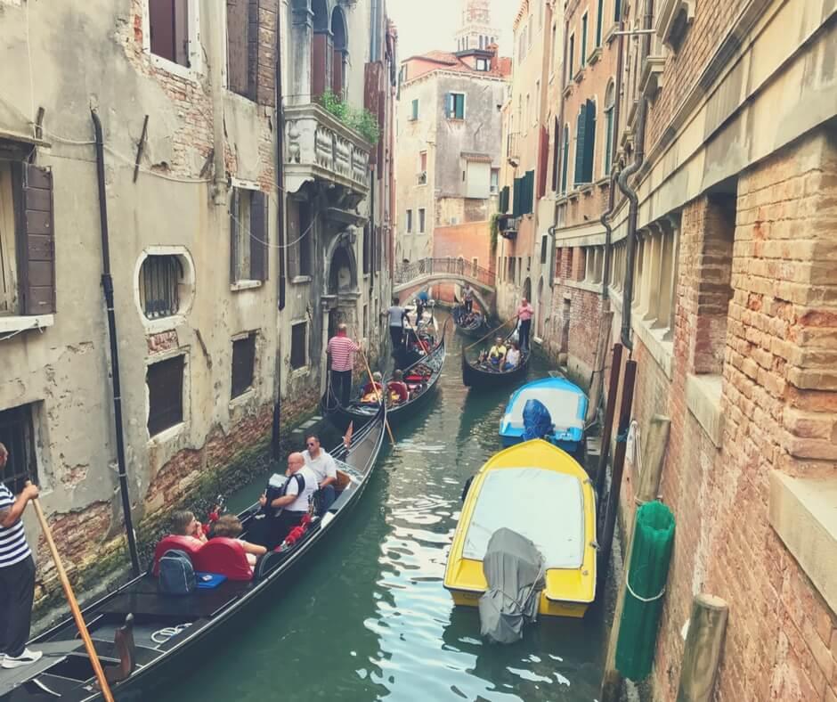 Canal in Venice, full of gondolas