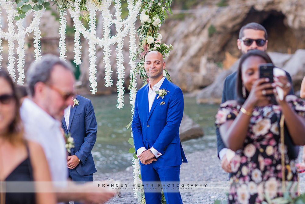 Groom smiling as bride walks down aisle