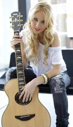 Foto de Nicole Natalino posando con su guitarra
