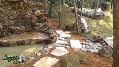 Bizzarri plantando a grama esmeralda junto ao lago de carpas com a mureta de pedra, com pedras ornamentais, tipo pedra moledo, com os caminhos de pedra com pedra cacão de São Tomé, obra em sítio em Nazaré Paulista-SP. 05 de abril de 2017.