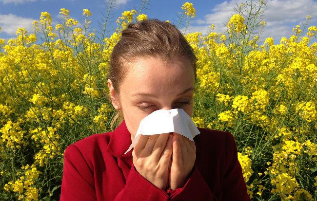 Donna allergica tra i fiori che si soffia il naso