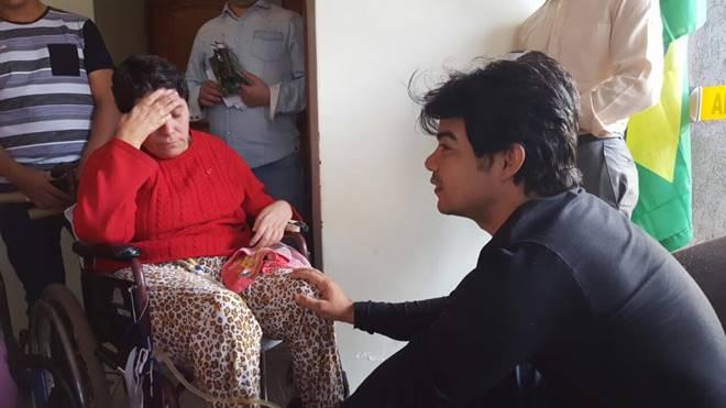 Samuel Mariano conversando com idosa em cadeira de rodas