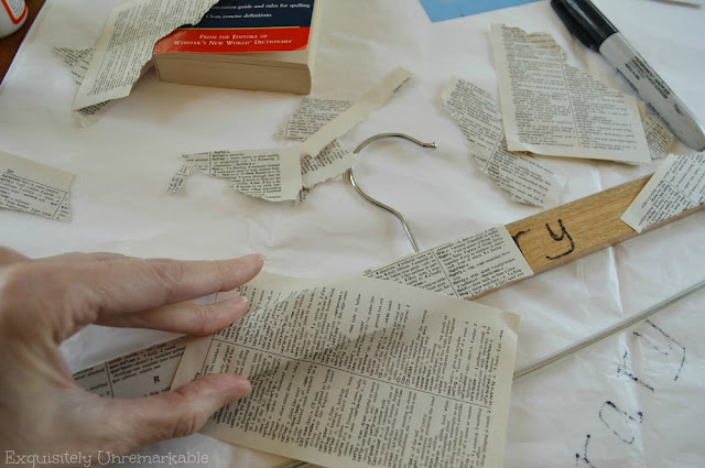 Covering a wooden hanger with book pages