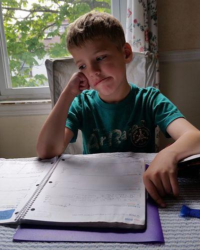 Deberes de los niños. Niño sentado a la mesa, intentando realizar su tarea escolar.