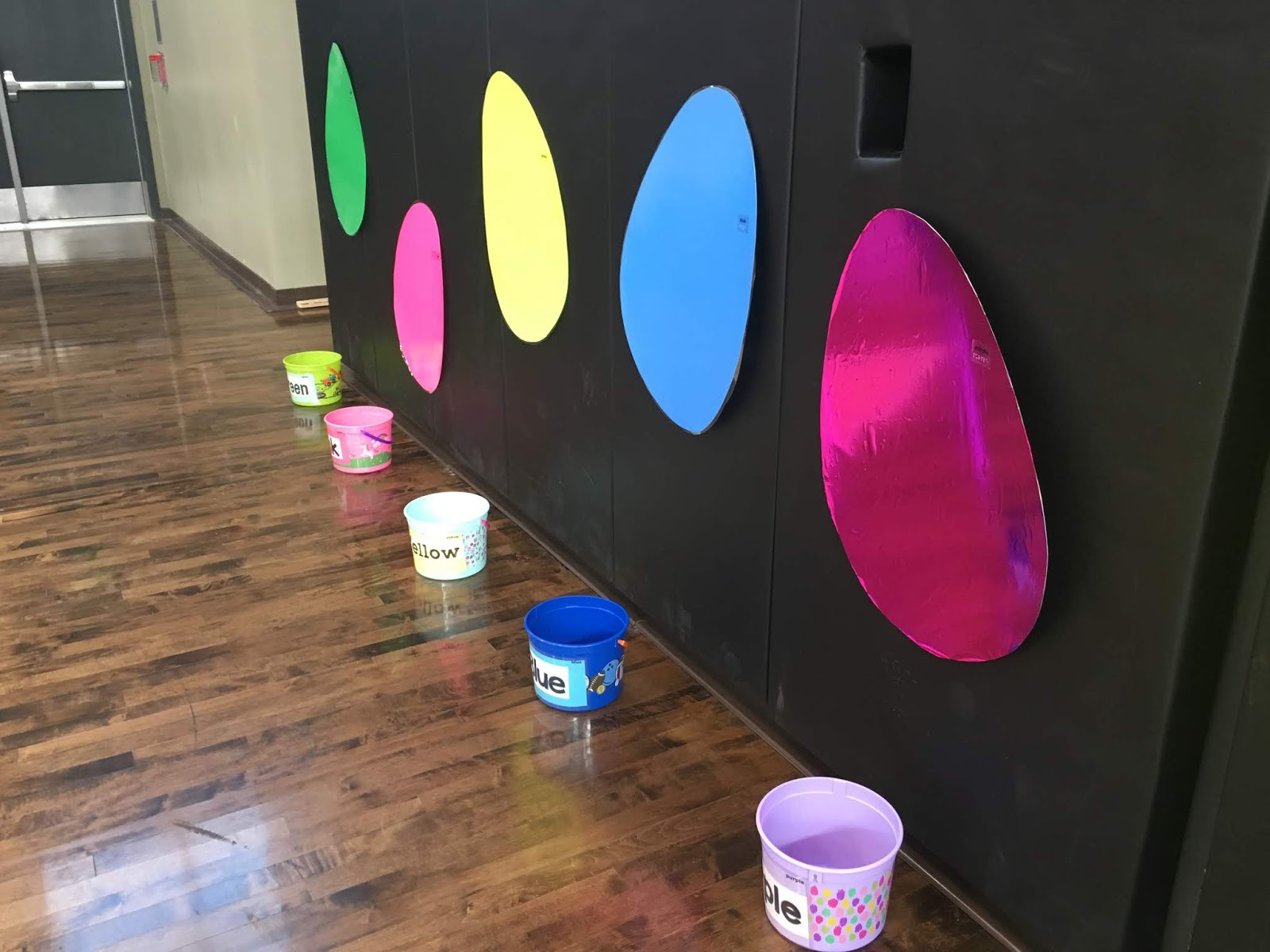 an image of a wall with large bright color eggs with buckets