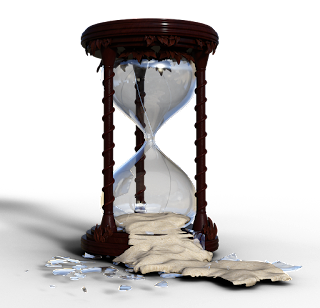 A broken hourglass with sand flowing from the bottom