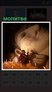 в пещере сидит монах и молится со свечами