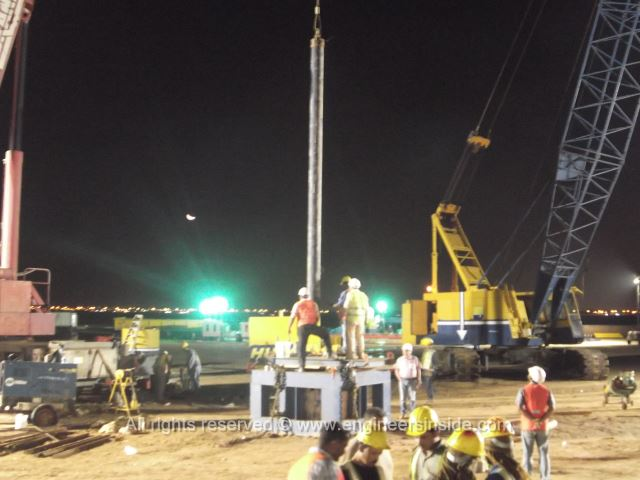 Workers and machines around test pile