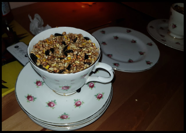 Filling teacups with birdseed and melted lard to give the winter birds a treat