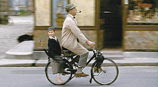 Jacques Tati on his bicycle with his iconic pipe from the movie Mon Oncle.