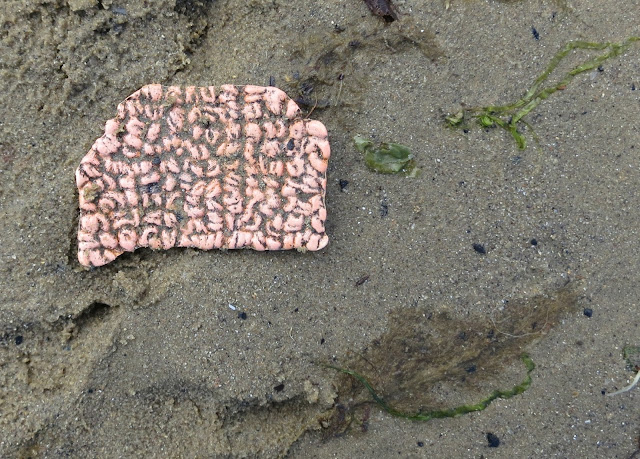 Fragment of something (don't know what) pink with grey (sand?) patterns.