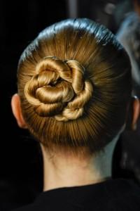 Die Haare werden ganz nach hinten getragen. Dann angeordnet, um sich wie ein Seil zu drehen. Diese Frisur sieht gepflegt und schlank aus.