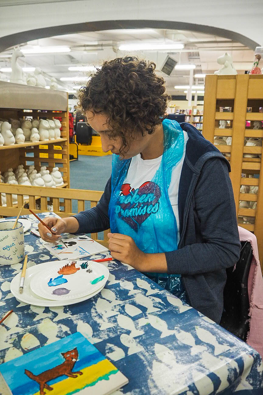 Travel blogger painting tiles at Poole Pottery