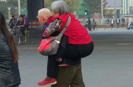 Buktikan Cinta, Pria Tua Ini Gendong Istrinya Untuk Menyebrang Jalan
