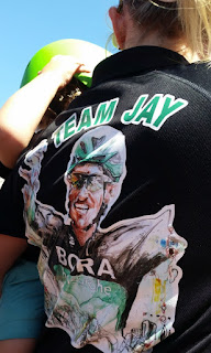 "The back of a black ""Team Jay"" Tee shirt that someone is wearing: it has an artist's drawng of Jay McCarthy in his bike riding gear, depicting his top half with his arms raised in victory. Large green block letters with whtie borders spell ""TEAM JAY"""