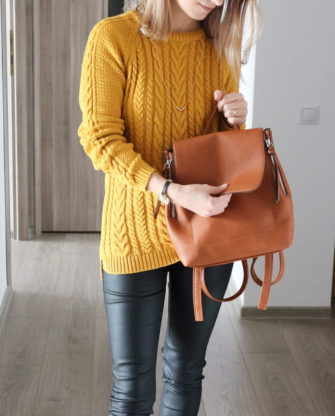 cosy knit with tan backpack and coated jeans