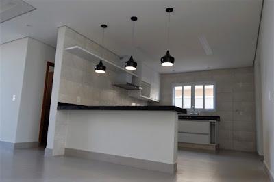 A cozinha planejada com balcão americano tem um nicho reservado para uma geladeira side by side, além de acesso prático para a lavanderia.