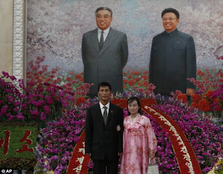 Couple poses in front of a mural of Kim Il Sung and Kim Jong Il