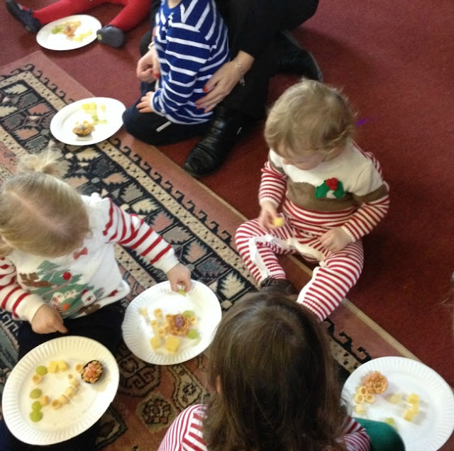 toddlers sat on floor with food on plates, one child taking food from anothers plate