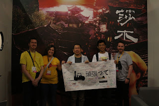 Yu at Gamescom posing with the banner and members of the Shenmue fan community.