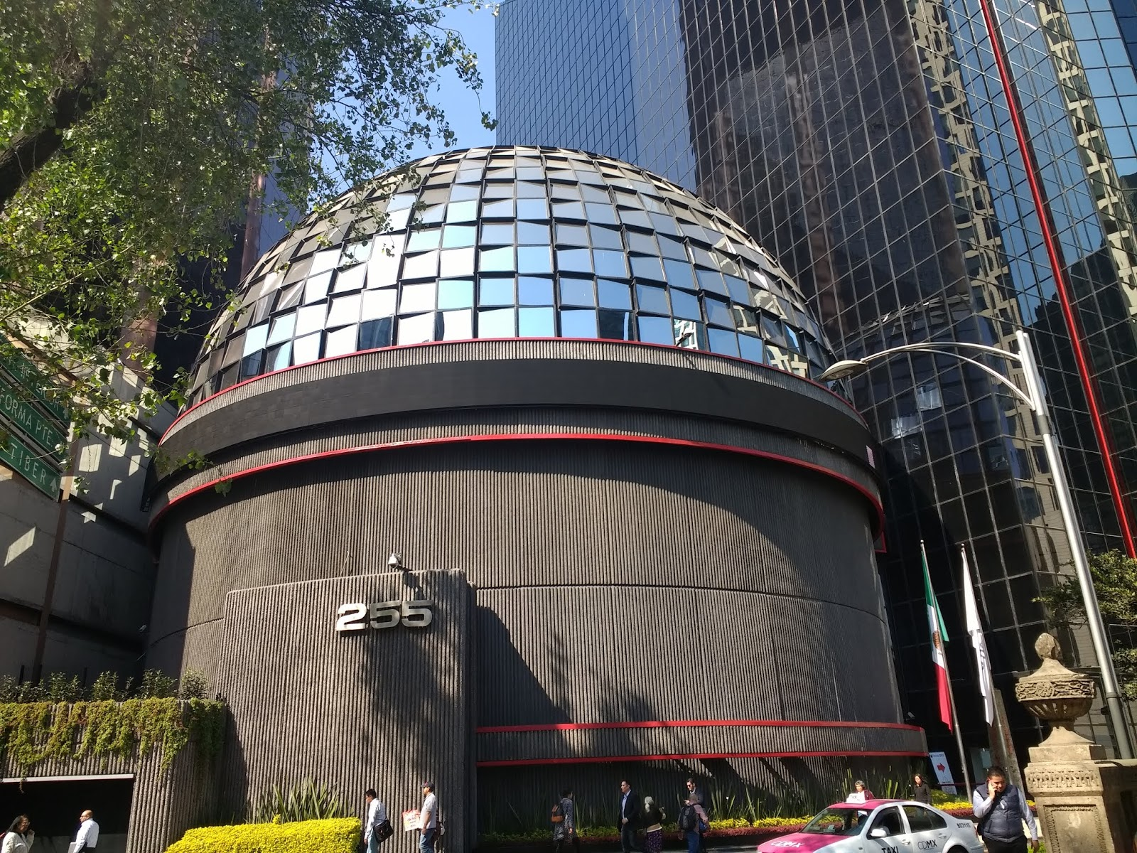 the mirror ball building in front of a futuristic pencil thin building comprised the city s bolsa de valores or stock exchange