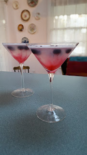martini made with limoncello, blueberry vodka and lemon juice garnished with frozen blueberries