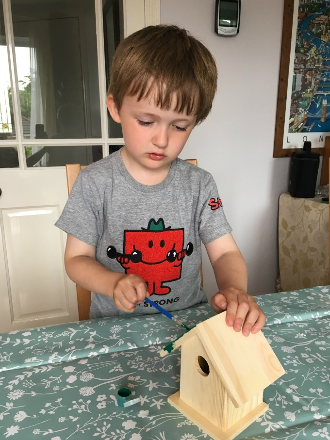BoxWild-Children's-Big-Bird-Gift-Box-Review-boy-concentrating-and-painting-roof-green