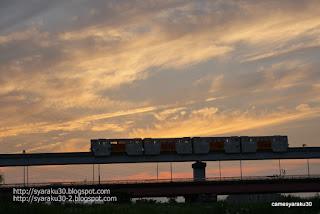 夕焼けを背に走るモノレール写真