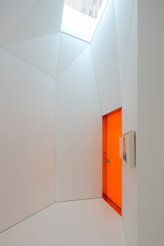 Orange entrance doors and white hallway