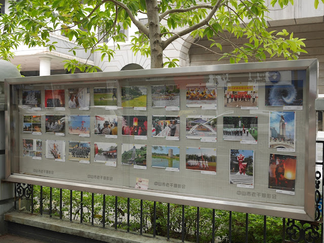 Collection of photographs by the Zhongshan Veteran Cadre Photography Association (中山市老干摄影会) posted outside