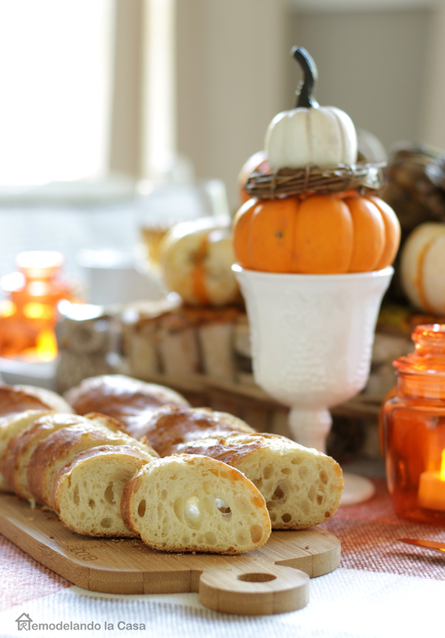 sliced bread on cutting board with orange lanterns and pumpkin centerpiece