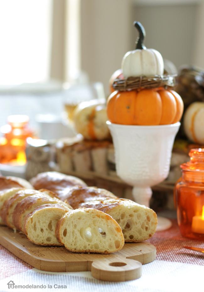 sliced bread on cutting board with orange lanterns and pumpkin centerpiece