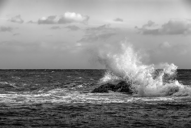 Dorset coast image in monochrome of waves smashing against a rock