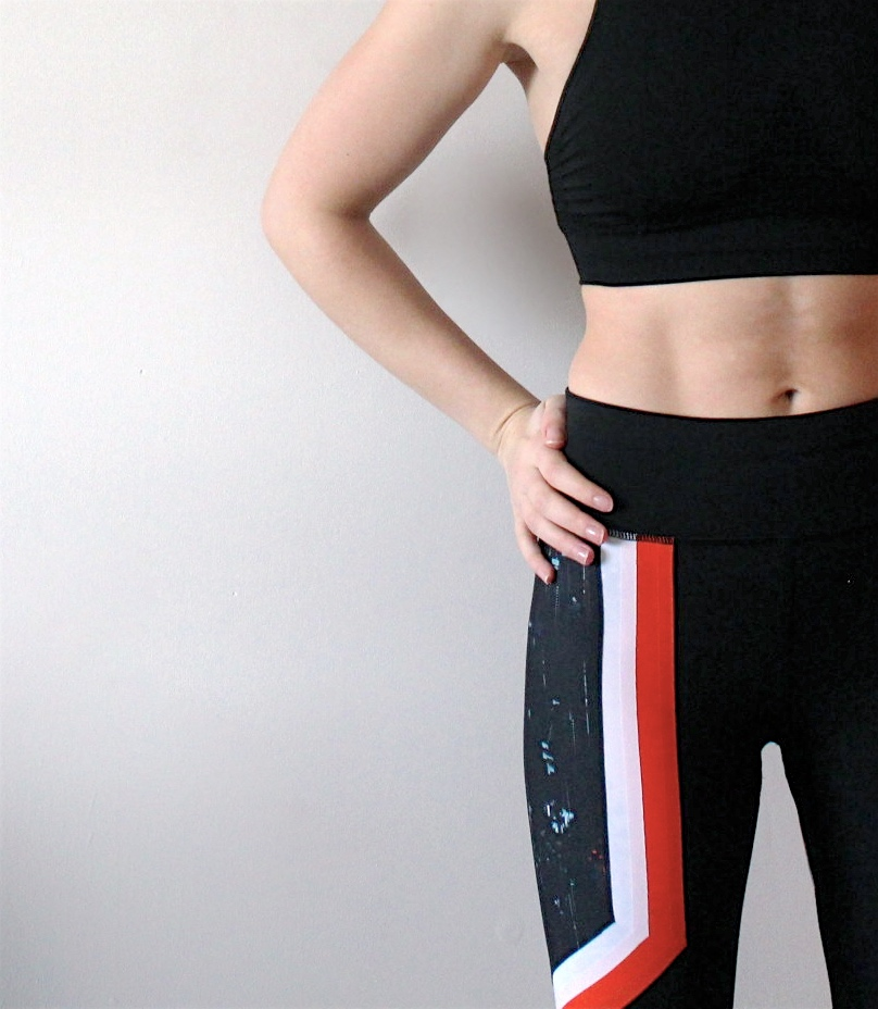 Hand on hip shot of half the body, with black crop top and black leggings with orange detail