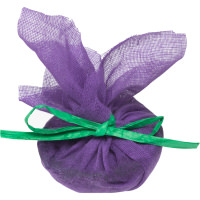A purple semicircular bath melt with pieces of golden brown oats, black raisins, tied up in a purple mesh bag on a white background