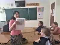 бібліотекар показує школярам українські поштові марки