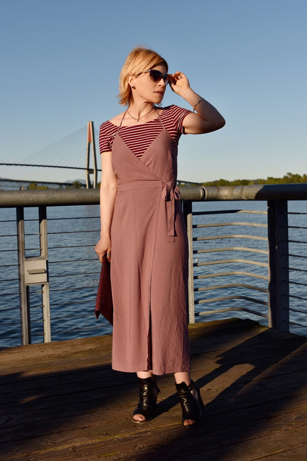 styling a mauve wrap slipdress over a striped tee, with cutout booties and an envelope clutch