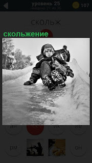 По ледяной горке скольжение мальчика на ногах вниз, придерживаясь рукой