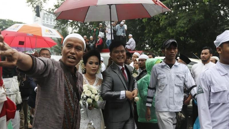 Pengantin yang akan menikah di Katedral dipayungi massa aksi 112