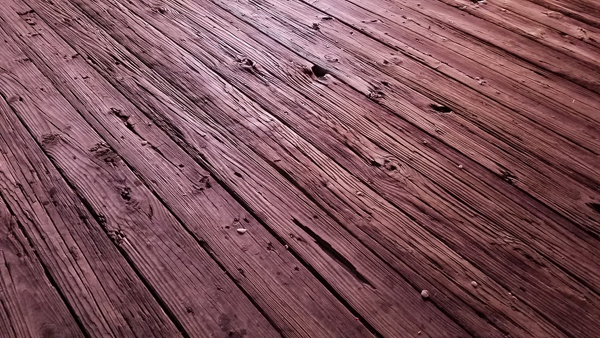 image of weathered wooden planks on a Jersey Shore boardwalk, with a red hue from the lights of the stores, offscreen
