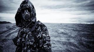Persona con capucha y máscara de gas en un páramo.