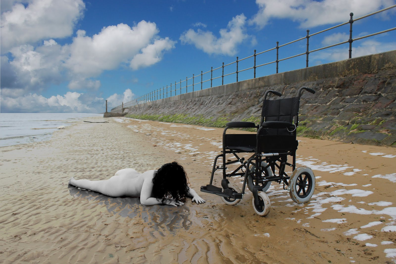 Picture of Kaliya Franklin on a beach, out of her wheelchair